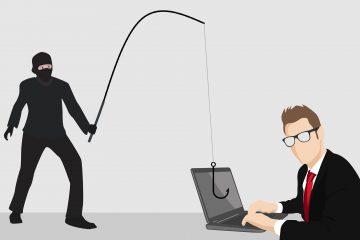 oszustwo internetowe, człowiek przy laptopie, a niedaleko niego zamaskowany czarny mężczyzna rzuca hak na jego dane i pieniądze