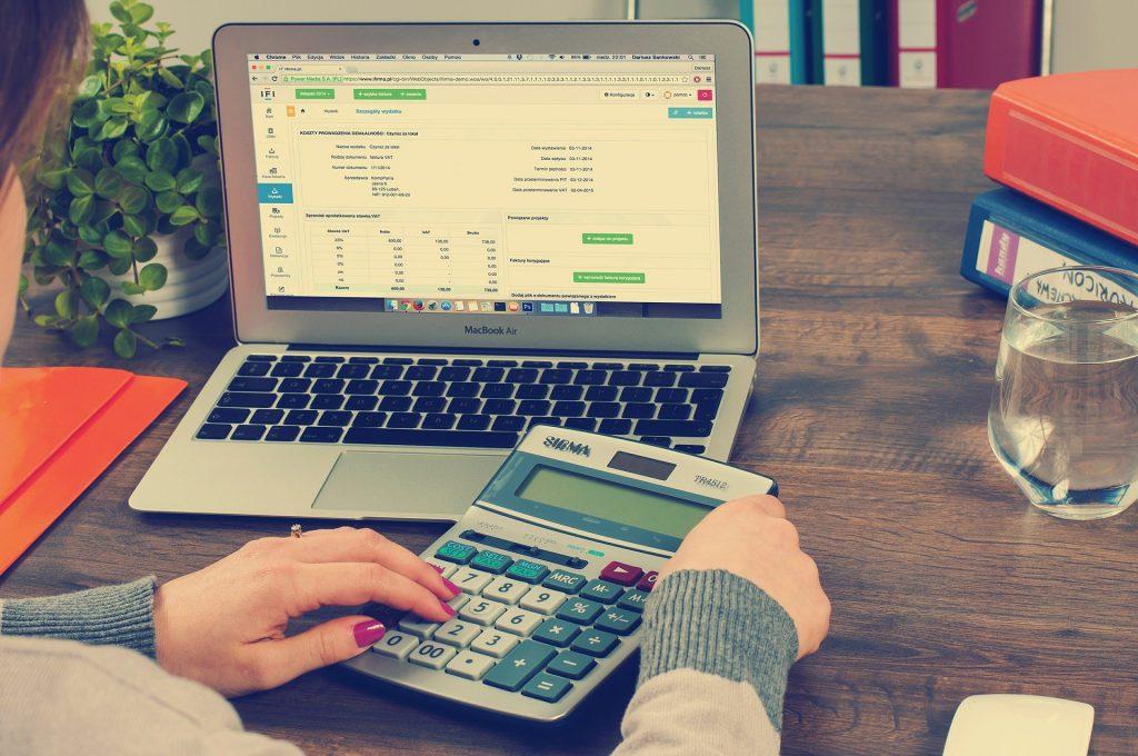 osoba przy laptopie rozliczająca podatki na kalkulatorze oraz przez Internet